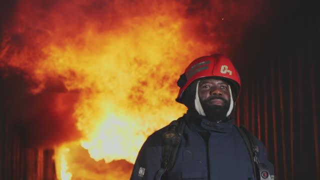 slo mo brandman, brandman gå mot kameran med eld rasar i bakgrunden. - släcka bildbanksvideor och videomaterial från bakom kulisserna
