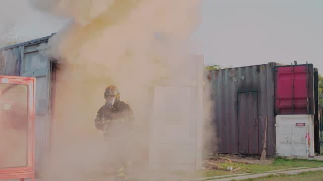 brandman, brandman gå mot kameran med eld rasar i bakgrunden. - släcka bildbanksvideor och videomaterial från bakom kulisserna