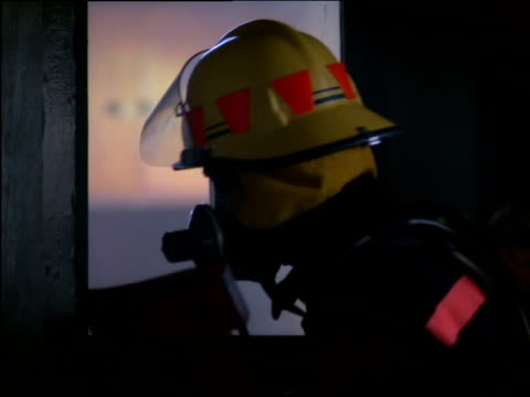 stockvideo's en b-roll-footage met fireman holding an axe peers through broken window assessing fire - bijl