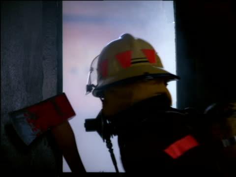 stockvideo's en b-roll-footage met fireman holding axe peers through broken window checking room beyond for danger - bijl