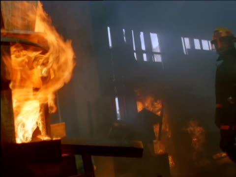 fireman pulls down burning piece of furniture - burning stock-videos und b-roll-filmmaterial