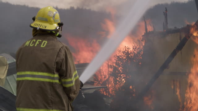 fireman shoots a powerful stream of water onto a raging structure fire - myrtle creek stock videos and b-roll footage
