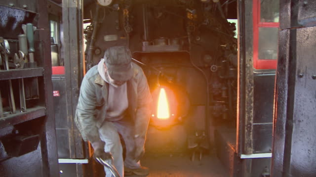 MS Fireman shoveling coal into fire in steam engine 7470, North Conway, New Hampshire, USA
