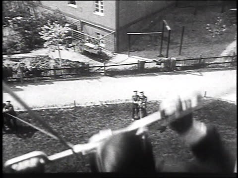 1930 montgage fireman sliding on pulley down rope from window to test rescue technique, may 14, 1930 / berlin, germany  - flüchten stock-videos und b-roll-filmmaterial