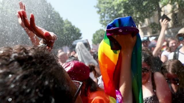 fireman spray revelers with water as the paris gay pride march takes place in sweltering temperatures of 36 degrees which this year commemorates the... - one parent stock videos & royalty-free footage