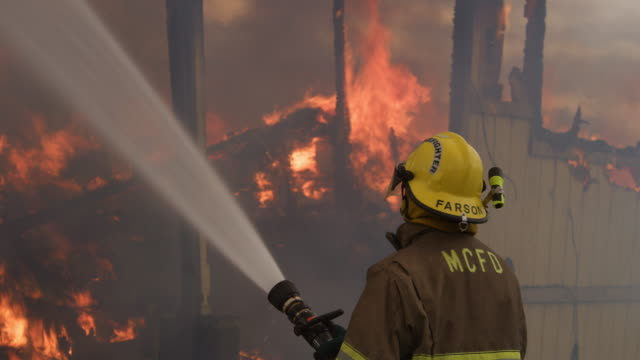 fireman spraying water on the fiercely burning interior of a structure almost demolished by flames - myrtle creek stock videos and b-roll footage