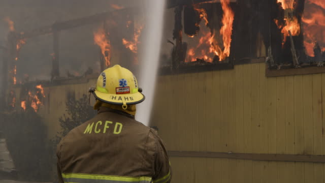 fireman using a hose in front of a burning house - myrtle creek stock videos and b-roll footage