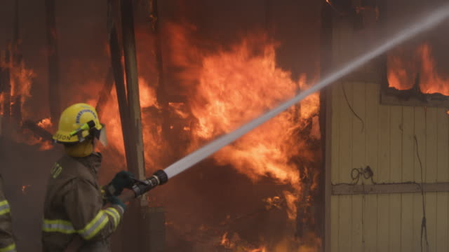 fireman using a hose on a fiercely burning house fire, other firemen walk by - myrtle creek stock videos and b-roll footage