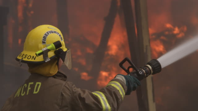 fireman using a hose on flames of a structure engulfed in fire - myrtle creek stock videos and b-roll footage
