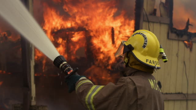 fireman using a hose on the fiercely burning remains of a house - myrtle creek stock videos and b-roll footage