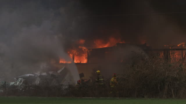 firemen aim hoses to rain down water onto a house engulfed in flames - myrtle creek stock videos and b-roll footage
