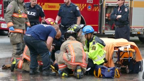 vídeos y material grabado en eventos de stock de firemen and ems crews working on patient in the street - primeros auxilios