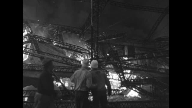 firemen and other men in front of burning wreckage / shot from front of wreckage fire and smoke in background / closer shot of men walking back and... - airship stock videos & royalty-free footage