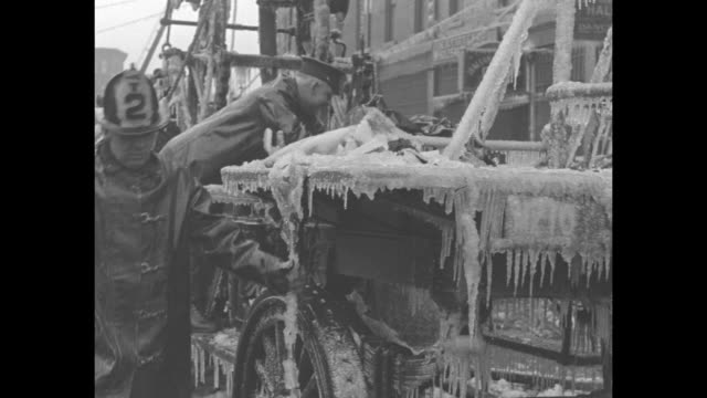 stockvideo's en b-roll-footage met firemen carry hose long hose past row houses covered in ice from frozen firehose water / firemen steam pumper fire engine covered in ice / steam... - fire hose