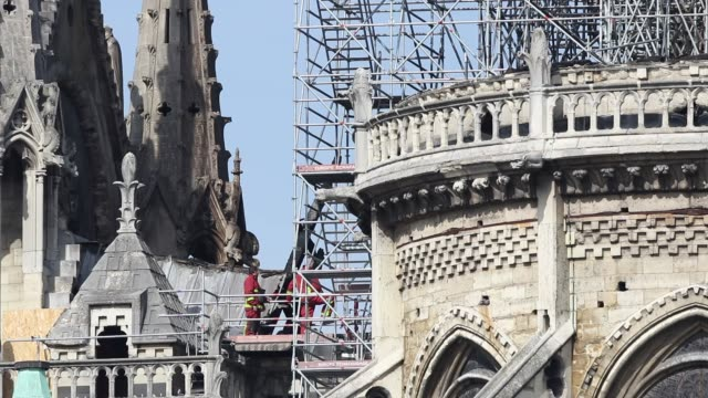 firemen carry out inspections at notre-dame cathedral following a major fire on april 16, 2019 in paris, france / a fire broke out on monday... - spire stock videos & royalty-free footage