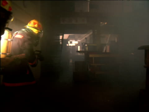 vídeos de stock e filmes b-roll de firemen carrying hoses walk through smoke filled warehouse lighting their way with torches - smoke physical structure