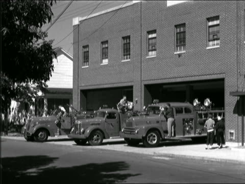 b/w 1952 firemen cleaning fire trucks in front of station house / two children ride by on bicycles - 1952 stock videos & royalty-free footage