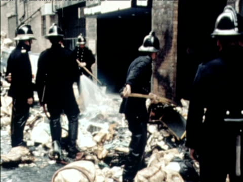 firemen extinguish fire and sweep up rubbish during dustmens strike soho london 1970 - employment issues stock videos & royalty-free footage