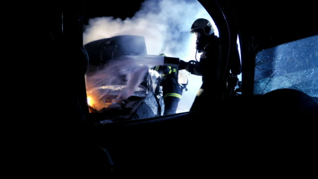 pov firemen extinguishing car fire with foam viewed from the other car involved in the accident at night - firefighter stock videos and b-roll footage