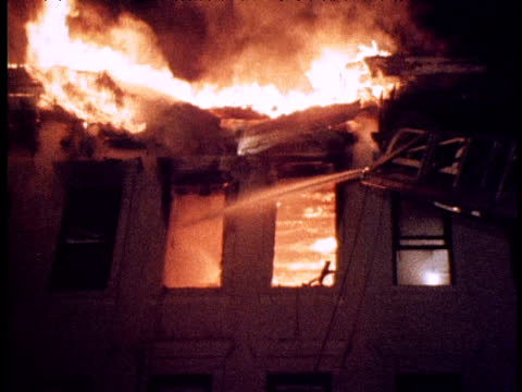 firemen fight blaze in apartment block; 1970s - flammenmeer stock-videos und b-roll-filmmaterial