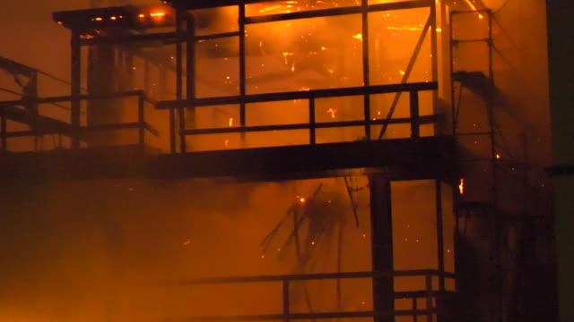 vídeos y material grabado en eventos de stock de firemen fighting to put out a fire on house under construction at night in a neighborhood. - incendios provocados