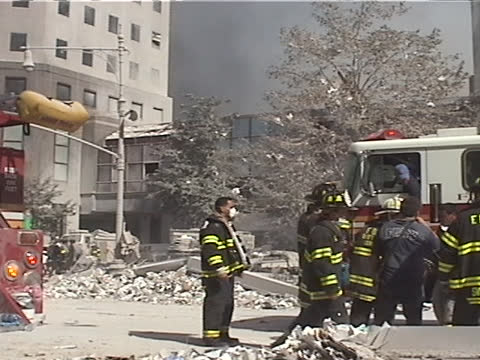 stockvideo's en b-roll-footage met firemen gather at a fire truck during the late afternoon on september 11th, 2001 in new york city, usa. the september 11 attacks, often referred to... - september 11 2001 attacks
