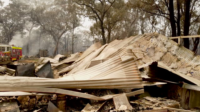 firemen inspect a house recently destroyed by bushfires on the outskirts of the town of bargo on december 21, 2019 in sydney, australia. a... - damaged stock videos & royalty-free footage