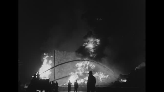 stockvideo's en b-roll-footage met [3/15/1949] firemen silhouetted against fire at night shooting streams of water onto fire at us army warehouse full of munitions / [3/16/1949]... - munitie