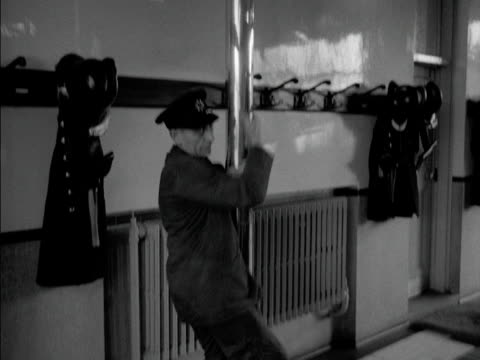 Firemen slide down a pole and rush to their fire engine at Ealing fire station