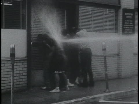 firemen spraying african american citizens with high pressure fire hoses. - fire hose stock videos & royalty-free footage