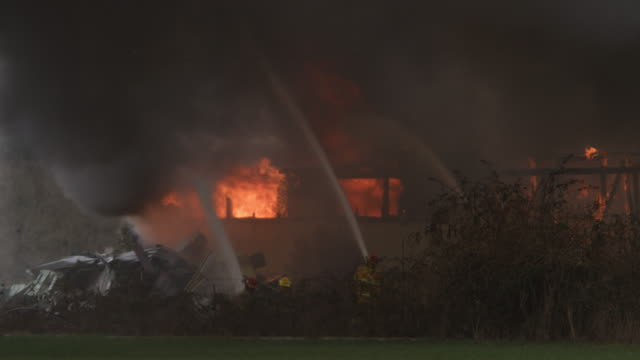 firemen spraying water on a house engulfed in flame - myrtle creek stock videos and b-roll footage