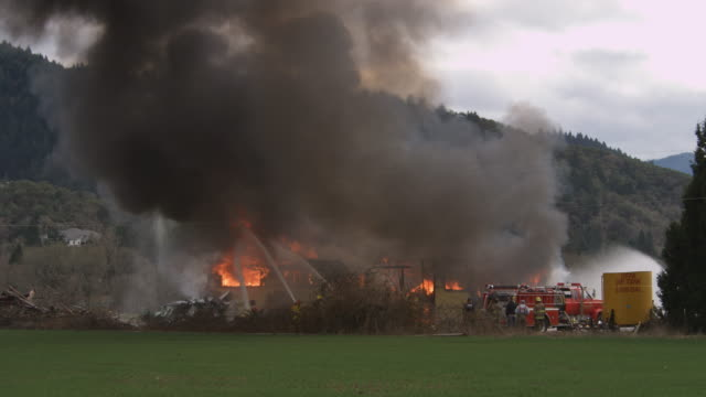 firemen spraying water on a house engulfed in flames - myrtle creek stock videos and b-roll footage
