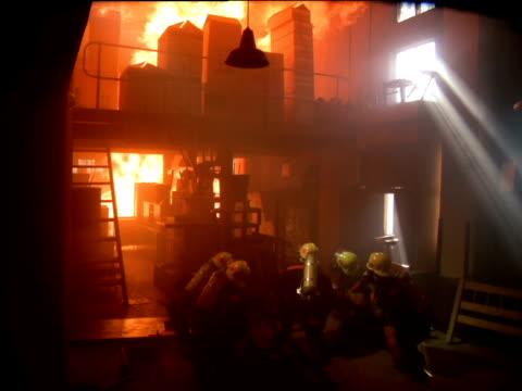 vídeos de stock e filmes b-roll de firemen squat down observing fire consuming boxes in warehouse - smoke physical structure