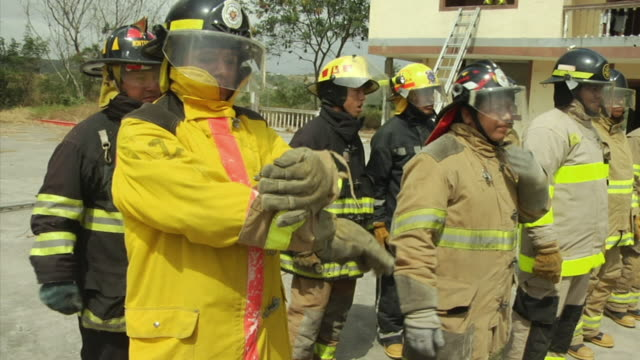 ms pan firemen standing in line listening to instructor, ecuador - ecuador stock videos and b-roll footage