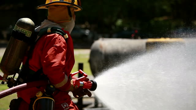 vídeos de stock e filmes b-roll de firemen using extinguisher and water from a hose for firefighting.firefighter wearing a fire suit for safety under the danger case. - mangueira