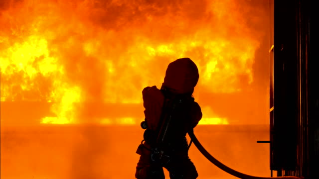 vídeos de stock e filmes b-roll de 4k firemen using fire hose to extinguish a fire inside burning building - carro de bombeiro