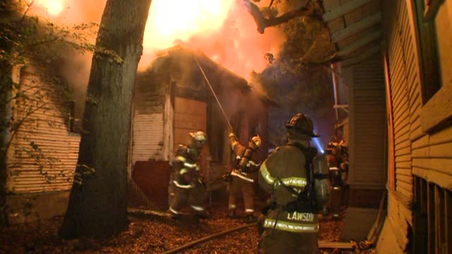 firemen using hose on house fire - firefighter stock videos and b-roll footage