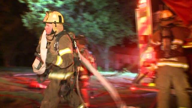 vídeos y material grabado en eventos de stock de firemen using hose on house fire - parque de bomberos