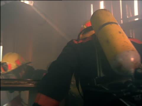 vídeos de stock e filmes b-roll de firemen walk through dark warehouse filled with smoke using torches to light their way - smoke physical structure