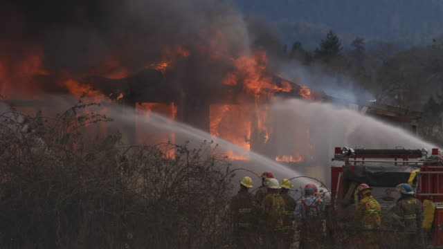 firemen watch as streams of water are played on a fiercely burning house - myrtle creek stock videos and b-roll footage