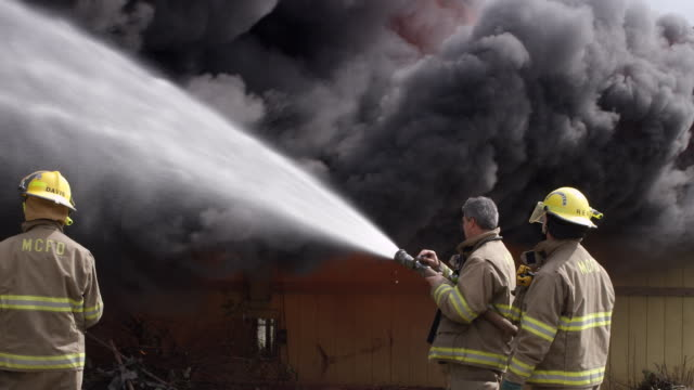 Firemen watch while one of them uses a hose as rolling black smoke partly conceals leaping flames above a burning house