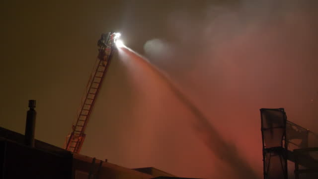 stockvideo's en b-roll-footage met firemen with a hose on a ladder crane fighting to put out a house fire at night in a neighborhood. - fire hose