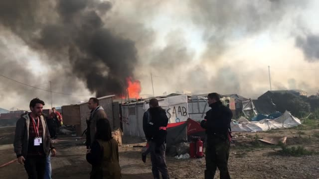fires continue to rage in the jungle camp as authorities demolish the site on october 26 2016 in calais france demolition work continues at the... - flüchtlingslager stock-videos und b-roll-filmmaterial