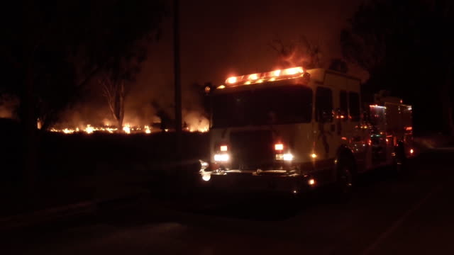 ws firetruck and burning brush fire at night - rescue worker stock videos and b-roll footage