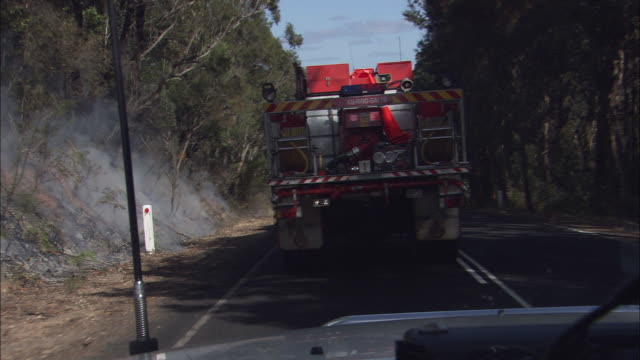 a firetruck drives down a rural road past smoldering brush fires and firefighters with another truck. - firefighter stock videos & royalty-free footage