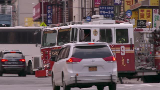 nyfd firetruck with its sirens on racing through chinatown - 消防車点の映像素材/bロール
