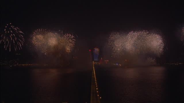 vídeos de stock e filmes b-roll de fireworks burst above a coastal skyline. - 2000