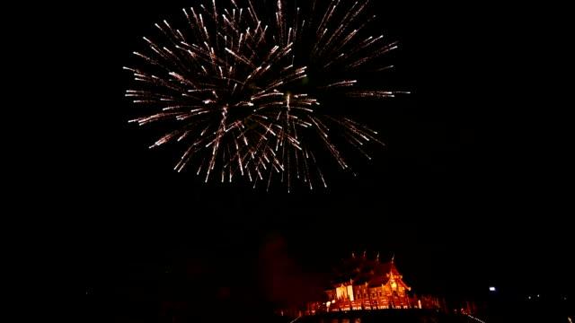 vídeos de stock e filmes b-roll de fireworks celebrate the new year 2018 at rajapruek royal park, chiang mai with beutiful light of hor khum luang temple,thai tradition building. - casa de jardim