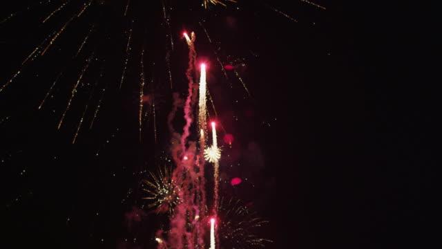 vídeos y material grabado en eventos de stock de fireworks display of rockets trailing pink smoke and starbursts raining sparks  - sparks