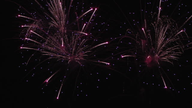 fireworks display with colorful starburst explosives exploding in the night sky, rockets shot up from lower frame bursting, glowing, sparkling and streaking on holiday event - firework display stock videos & royalty-free footage
